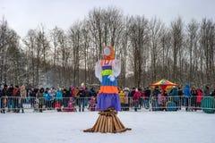 Gatchina Ryssland - Februari 18, 2018: Shrovetide festmåltid Maslenitsa En stor docka är klar för att bränna Åskådarna Royaltyfri Bild