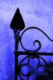 Gate. Iron Gate against blue wall Royalty Free Stock Images