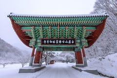 Gate of Baekyangsa Temple and falling snow, Naejangsan Mountain in winter. Royalty Free Stock Photography