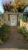 Gate with blocked entrance. Entrance to stone walled garden blocked by tshirt pinned to board Royalty Free Stock Images