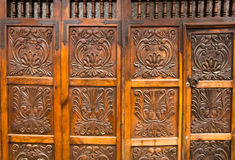 Gate. A carved wooden gate and door of an old house Royalty Free Stock Images