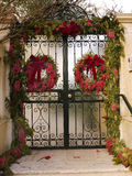 Gate with Christmas decorations. Wrought iron gate with Christmas wreaths Stock Photo