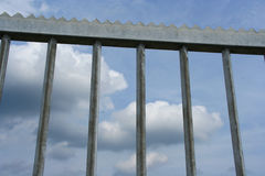 Gate closed. Cloudy sky behind bars royalty free stock photography