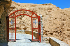 The gate with a cross on a mountain road Royalty Free Stock Image