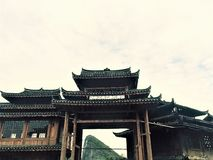 The gate of the ethnic village of China surrounded by mountains royalty free stock photography