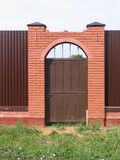 Gate in fence with brick pillars Royalty Free Stock Image
