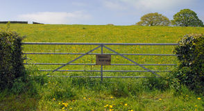 Gate into field showing a private keep out sign. A metal gate across access to a farmers field with a sign showing a private keep out stock image