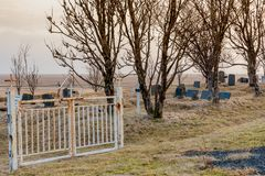 Gate into the Kalfafellsstadur Church graveyard in Iceland with crosses, headstones and long grass. Covering the mounds of graves royalty free stock photography