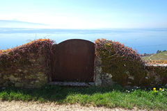 Gate of Lake Leman. A rustic old gate of a stone wall covered in moss and vines looks out towards Geneva on the vineyards of Lake Leman in Switzerland Stock Image