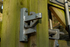 Gate lock. A metal gate lock fixed to a wooden post and gate showing the locking mechanism Royalty Free Stock Photography