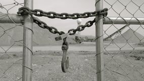 A gate locked with a chain, padlock and a hook. A monochrome view of a moon-like gravel making plant with a ball of water tower in the distance, with a heavy Royalty Free Stock Photo