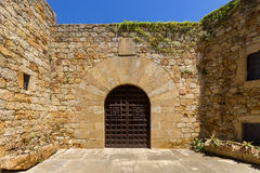 The gate in a medieval city. Wooden gate in the medieval town of Pals, Spain royalty free stock photography
