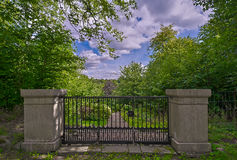 Gate. Old cast-iron gate with stone pillars Stock Images