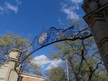A gate with an openwork wrought-iron arch on the background of a blue sky and a green tree. KIEV - UKRAINE - APRIL 2017: Logo of National Technical University of Royalty Free Stock Photos