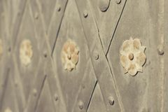 Gate with rivets and ancient style steel flowers Royalty Free Stock Images