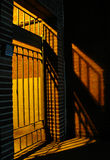 Gate and shadows at night. Secure gate backlit at night with shadows and keypad Royalty Free Stock Photos