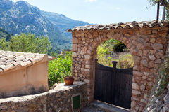 Gate on the street old traditional houses village, Fornalutx, Ma. Narrow street old traditional houses village with flowers, Fornalutx, Majorca island Stock Photo
