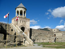 Gate of Svetitskhoveli Cathedral in Mtskheta, Georgia. Sunny day wiyh blue sky and clouds. Georgian national flag white with red cross. Ancient fortress, a Stock Images