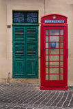 Gate and a telephone cabin. Traditional english style of a red telephone cabin. In the background green old gate. Street of fishing village Marsaxlokk on the Royalty Free Stock Image