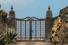 Gate to the cactus garden. A beautifully wrought gate leads into the cactus garden Stock Photo