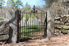 Gate to cemetery. Granite post with black wrought iron gate to cemetery Stock Image