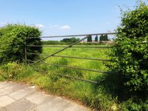 Gate to a farm field. Metal gate with hedgerows on either side leading to a field, Saughall Massie, Wirral Royalty Free Stock Photo