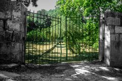 Gate to the Forest. A iron gate in black and white being the entrance to the forest Stock Photo