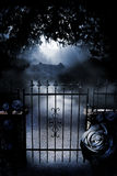 Gate to moonlit mansion. A black rose framed iron gate closed in front of a road that leads to a mansion on a large property. The moon lights the scene in a blue Stock Photography