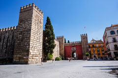 Gate to Real Alcazar Gardens in Seville. Sevilla, Spain - September 09, 2015: View to the gate to Real Alcazar Gardens in Seville. Tourists walking on sunny royalty free stock photos