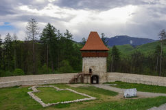 Gate tower of medieval fortress in Rasnov with mountains at back Royalty Free Stock Images