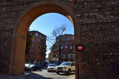 Gate in Verona fortress wall Italy. Gate in old Roman fortress wall and cars driving on road under it-remarkable example of successful coexistence of ancient stock image