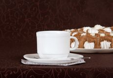 Gateau, cup, saucer and spoon. Against a brown cloth Royalty Free Stock Image