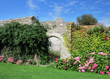 Gated arch through a Medieval Garden wall Royalty Free Stock Images