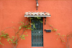 Gated Door. Of red Spanish building, with tile roof and light fixture above stock photos