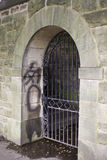 Gated Doorway with Graffiti. Decorative arched wrought iron gate in an old block stone doorway.  Graffiti on inside of of doorway to the left Royalty Free Stock Image