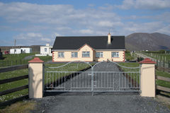 Gated drive and house. Gated drive and Irish house next to a rural track with distant mountains. Achill Island, Ireland Royalty Free Stock Photography