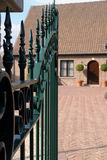 Gated Entrance. Open wrought iron gate leading to the front of a home Stock Photos