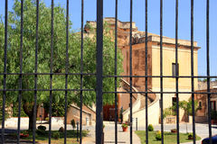Gated estate. A view through the bars of a security gate into a building compound of an elaborate estate on a bright, sunny day Royalty Free Stock Photos