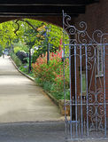 Gated secret garden. Photo of a gated secret garden with scroll design metalwork gate leading to a beautiful landscaped garden Stock Photos