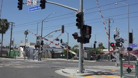 Gates closing at a train crossing in the city. Train crossing gates closing before the commuter train crosses the intersection stock footage