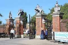 Gates of the Hampton Court Palace, UK. HAMPTON COURT, GREAT BRITAIN - MAY 18, 2014: This is the gates of the Hampton Court Palace with the symbols of Great Stock Photos