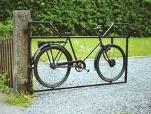 Gates made of bicycle. Lovely doors to village garden made of old black bicycle Royalty Free Stock Photography