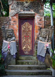 Gates of the old temple with stone guards. Indonesia, Bali. Stock Images