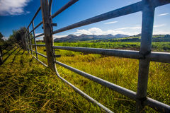 Gates to Mourne Mountains. A view of a field with a gate and the Mourne Mountains in the background in Northern Ireland stock photo