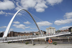 Gateshead Millennium Bridge &. The Millennium Bridge that spans the River Tyne between Gateshead and Newcastle, England.  The arch to the left supports the Stock Photo