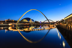 Gateshead Moonlit Evening. The image shows the Gateshead Millennium Bridge on a moonlit evening. In the background are the Sage and the Tyne Bridge royalty free stock photography