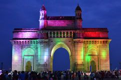 Gateway of India in Mumbai. Groups of people visiting Gateway of India, colored lightnings in the night. Overlooking Arabian Sea the arch was build commemorate Stock Photography