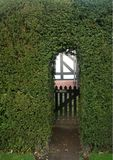 Gateway no entry. Hidden wooden gateway set in Yew hedge with 'no entry' sign. Copy Space Stock Photo