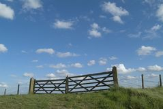 Gateway to . . .?. Two farm gates and barbed wire fence set against a blue sky with clouds royalty free stock photos