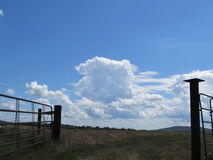 Wide Open Farm Gate, Blue Sky and Rural Landscape. Storm clouds forming to our SW made for a pretty picture through the open gate to one of our pastures royalty free stock photography